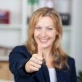 Bureau de connexion de gesturing thumbs up de femme d affaires Photographie stock libre de droits