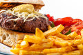Burger with chips and tomato beef tomatos in the background cheese melted over top mustard placed on toasted bread Royalty Free Stock Images