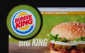 Burger king photo of homepage on a monitor screen through a magnifying glass Royalty Free Stock Image