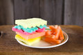Burger made from sponges different colors on wooden bacground. Concept of unhealthy food and non-natural products