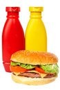 Burger with mustard and ketchup bottles