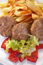 Burgers with fries salad and peppers Stock Image