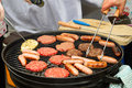 Burgers and sausages on barbecue Stock Image