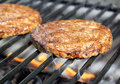 Burgers sizzling on the grill juicy cooking over flames barbecue Royalty Free Stock Image