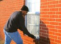 Burglar breaking in home window african american male the act of into a through a Stock Image