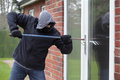 Burglar breaking into a house window patio door with a crowbar Stock Images