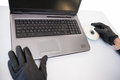 Burglar hacking and putting a cd rom in laptop on white background Stock Photography