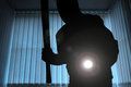 Burglar or intruder at night inside of a house office with flashlight and baseball bat Stock Photo
