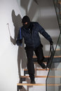 Burglar laying in wait a masked lying for his victim on the stairs Stock Images