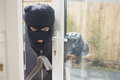 Burglar looking if someone is into the room in house Royalty Free Stock Image