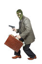 Burglar sneaking with the gun and a briefcase full of money isolated over white background Royalty Free Stock Photos