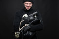 Burglar with stolen goods angry holding while smiling against black background Royalty Free Stock Photos
