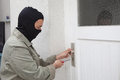 Burglar at work with mask opening a door on a private home Royalty Free Stock Photography