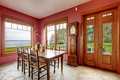 Burgundy dining room with antique clock spacious walkout deck furnished rustil old table set grandfather Royalty Free Stock Photography