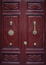 Burgundy door double with a brass knocker and handle Stock Photo