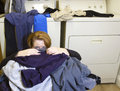 Buried in laundry mature woman sitting on the floor front of a washer and dryer the room covered dirty clothes Royalty Free Stock Image