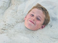 Buried in the sand up to neck happy boy Stock Photo