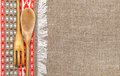Burlap background bordered by country cloth and utensils red green Royalty Free Stock Image