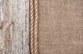 Burlap background bordered by rope and old wood rude Stock Image