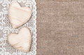 Burlap background with lacy cloth and wooden hearts white Stock Photos