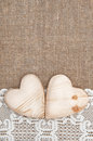 Burlap background with lacy cloth and wooden hearts white Royalty Free Stock Photos