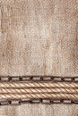 Burlap background with rope and metal chain textile Stock Image