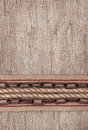 Burlap background with sacking ribbon, metal chain and rope Royalty Free Stock Photo