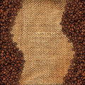 Burlap material with coffee beans Royalty Free Stock Photos