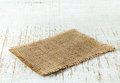 Burlap napkin on old wooden table Royalty Free Stock Photo