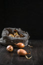 Burlap sack with onion on the wooden table. Royalty Free Stock Photo