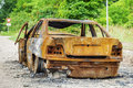 Burned down car wreck before crossroad Royalty Free Stock Photo