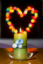 Burning candle amid colorful bokeh heart shaped Royalty Free Stock Photography