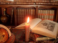 Burning candle, ancient books and globe. Royalty Free Stock Image
