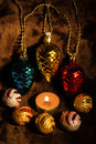 Burning candle and garland from glass cones balls on fur Royalty Free Stock Photography