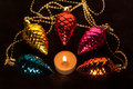 Burning candle and garland from glass cones on fur Royalty Free Stock Image