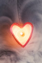 Burning candle heart in dense fog closeup view Royalty Free Stock Photo