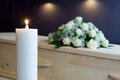 Burning candle in mortuary a with a coffin and a flower arrangement on the background a Royalty Free Stock Images