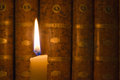 Burning candle and old books in the dark Stock Image