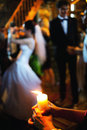 Burning candle wedding ceremony at religious bride and groom in background Royalty Free Stock Image