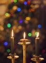 Burning candles on blurring Christmas lights background Royalty Free Stock Photo