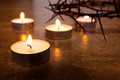 Burning candles four with crown of thorns on marble surface background with reflection close up scene copy space concept of memory Royalty Free Stock Photography
