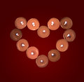 Burning candles in the shape of a heart on a red background Stock Image