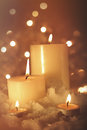 Burning candles in snow against sparkly background Royalty Free Stock Photography