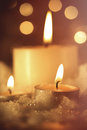 Burning candles in wet snow against sparkly background Royalty Free Stock Images
