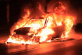 Burning car on the road Stock Image