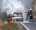 Burning car on the road Royalty Free Stock Images