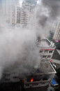 Burning fire in building is climbing up by pipe of the 。 lots of black and white smoke taken chongqing china Stock Photo