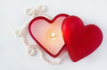 Burning heart candle with pearls in glass shaped box around it Royalty Free Stock Photography