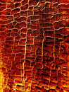 Burning hot wood texture of wooden surface with glowing cracks Royalty Free Stock Photography