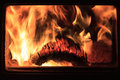 Burning log with flames in fireplace a glowing on fire surrounded by seen through the rectangular glass window of a modern wood Stock Photo